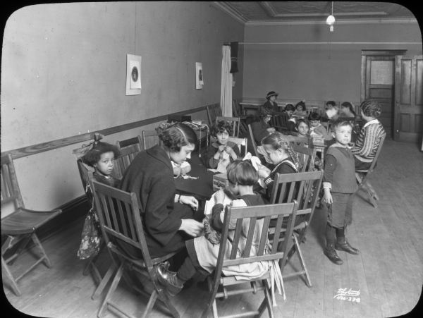 Groups of children seated at tables for a Saturday morning sewing group at Neighborhood House, with a woman helping the children at each table.