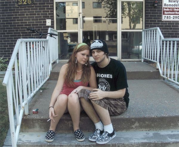 Portrait of a young woman, Crystal, and her friend, sitting on the steps of 326 South 7th Street. The friend is wearing a Ramones t-shirt, a hat, and shoes adorned with skulls.