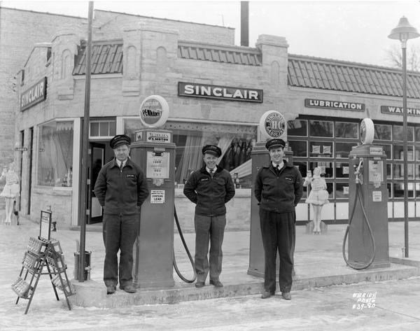 Three uniformed employees of the Sinclair Oil Company Service Station, located at 501 East Broadway, stand in front of the station's gas pumps. Two lifesize cutouts of women are in the background. The station was constructed in 1938.