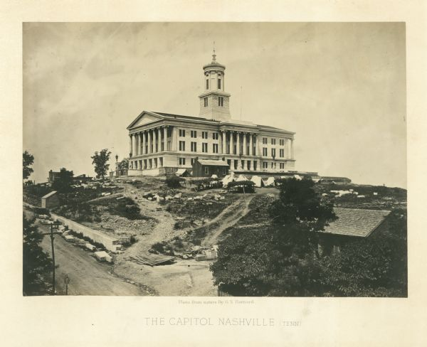 The Nashville, Tennessee capitol building is on a hill overlooking the city. Union soldiers have pitched tents on the grounds.