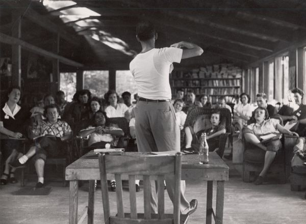 A man, with his back to the camera, is gesturing at and lecturing a student class, who are seated in a variety of chairs.