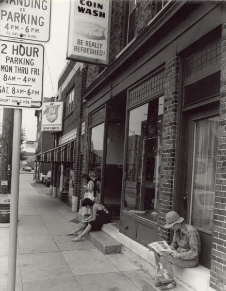 View down a sidewalk towards three people waiting outside of a coin laundromat on Williamson Street. Two women, one on steps of a doorway and another near a closed door, are sitting and reading newspapers. Next door to the laundromat is Star Liquor.
