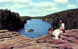 A woman in an Indian dress sits on High Rock overlooking a tour boat on the Wisconsin River.