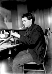 Portrait of the photographer J. Robert Taylor sitting at a table smoking a pipe and possibly woodworking.