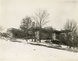 Southeast elevation of Taliesin in winter. Construction debris is scattered around the building base.