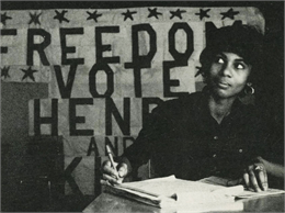 Unidentified black woman seated at a table. Banner reads 'Freedom Vote / Henry and King.'