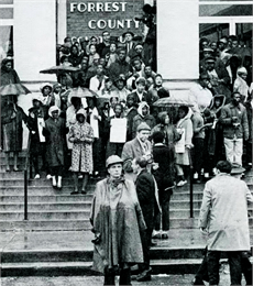 A black-and-white photograph showing a large crowd of demonstrators amassed on the steps of a courthouse.
