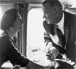 Lyndon Baines Johnson, the 36th President of the United States, is shown with his wife, Lady Bird Johnson, having an intense discussion, while seated in an airplane.