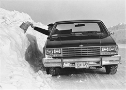 A mail carrier reaches over and almost through a snow bank to put mail into a rural mailbox.