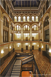 Interior of the ornate restored atrium of the hotel featuring arched windows and a glass ceiling.