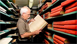 Harry Miller holding a large book with bookshelves behind him inside the Society Archives.