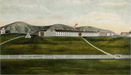 A view of Fort Crawford from the valley. A U.S. flag flies above the white hospital building.
