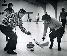 A man and a woman sweep the ice ahead of a curling stone.