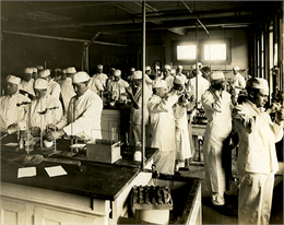 Men with white hats and aprons conducting scientific experiments.