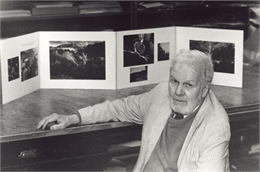 Paul Vanderbilt sitting in front of a display of his images and poetry.