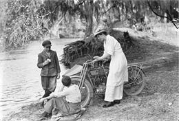 A woman leans against a Harley-Davidson near a lake.