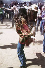 A young woman wearing a patterned blouse and blue jeans dances among a crowd of other audience members.