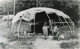 A Winnebago (Ho-Chunk) man and child inside a wigwam with the sides rolled up.