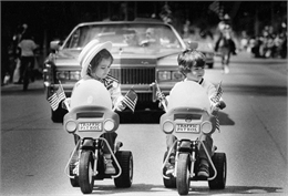 Two toddlers on bigwheels lead memorial day parade. A several cars from the parade are visible behind them.