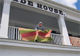 A woman airs out a handmade quilt from the balcony at the Wade House.
