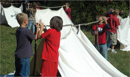Day camp participants setting up dog tents