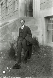 John R. Commons, a University of Wisconsin professor, is shown standing outside Sterling Hall with his hat on the ground at his feet.