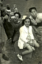 There is a girl sitting on a rock with two boys behind her who are clowning for the camera, and other children around them on the grass.