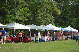 Tree-lined image with Wade House Arts & Crafts Fair vendors.