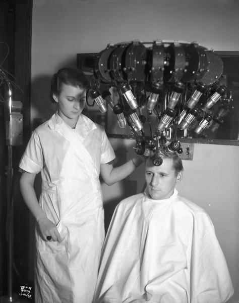 Cedric Parker, Capital Times reporter, gets his hair curled with a permanent wave machine attached to his hair, at Mrs. Wengel's Marinello Shop