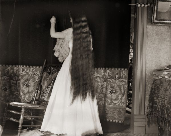 Edward Bass' wife, Ada, standing with her back to the camera. Her hair reaches to her knees..