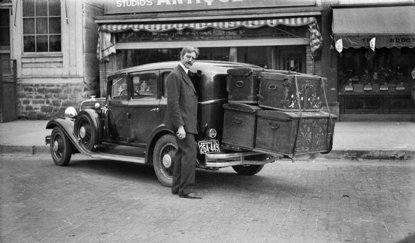 Ephraim Trimpey standing with a car loaded with four large trunks.