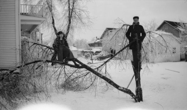 Harman Warner and Ethel Walker pose in the branches of a broken tree in winter. They are in the backyard, and houses can be seen behind them.