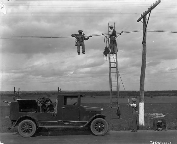 Two telephone line repair men hanging from a line, one of them on a ladder.