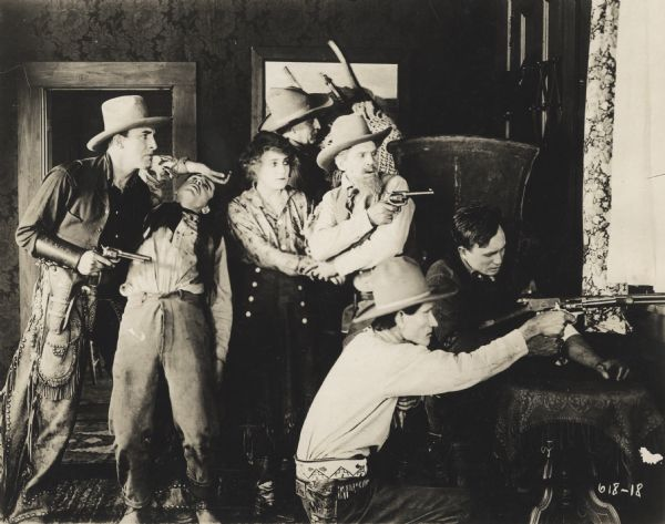 Actress Josie Sedgwick as Betty Clayton and six other men, some with guns, holed up in a ranch house, shooting toward a window.