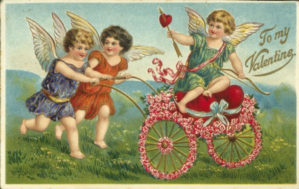 "Valentine's Day postcard with Cupid holding a bow and arrow seated in a two wheeled cart made of flowers, two cherubs are pushing it. They are in a meadow with hills in the background. Text on the right reads ""To My Valentine."""