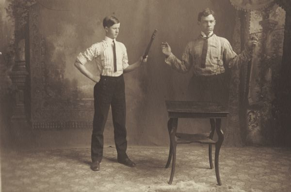 William R. Holmes, member of the Menomonie High School class of 1905, depicted as a professional magician in front of a painted backdrop. Pictured with a magic wand that resembles the leg of a chair, causing an assistant to disappear.