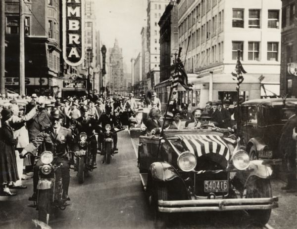 Franklin D. Roosevelt waving from a flag draped car surrounded by policemen on motorcycles.