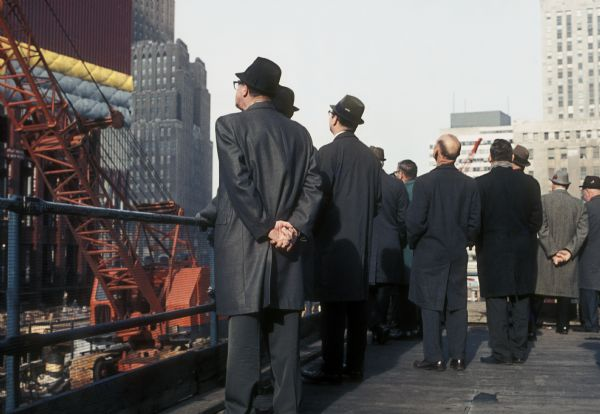 A group of men stands with their backs to the camera watching construction of the World Trade Center.