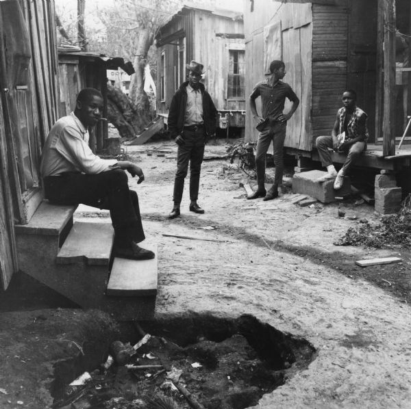 Two men sit outdoors on stoops of houses while two stand in the dirt pathway. More homes are visible in the background. There is a garbage or fire pit in the foreground.