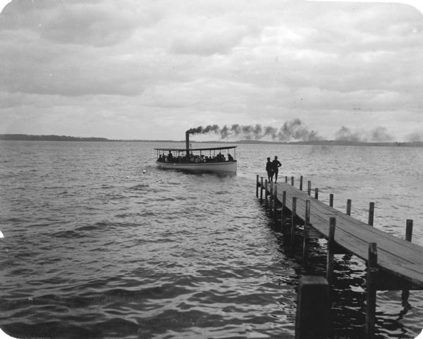 "The lake steamer ""Alice"" approaches the Madison dock on Lake Monona. Two boys wearing caps stand at the end of the pier."