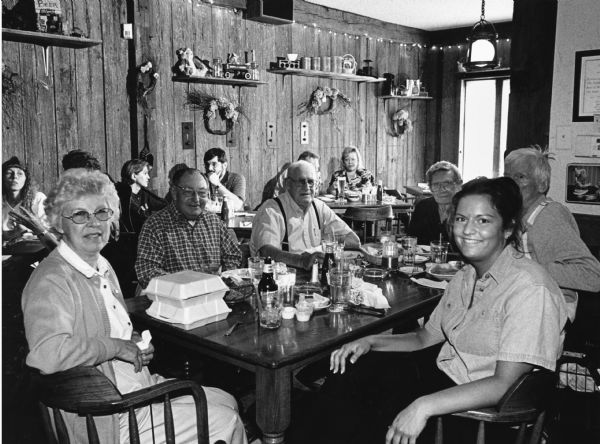 A table full of people pose for the camera in the Jail House Restaurant.