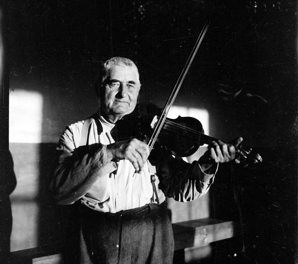 Emil Boulanger, staring straight into the camera, is posed holding his violin in playing position.