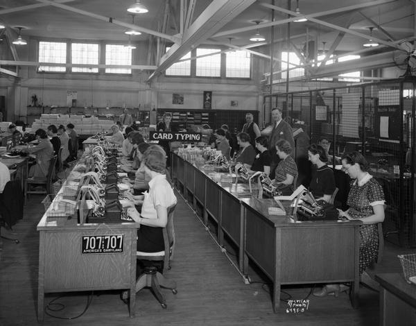 A view of rows of desks with women employees. Behind the work area two men, the supervisor and the Secretary of State Fred Zimmerman, stand.