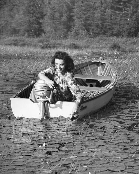 A woman in a boat is smiling into the camera in an ad for an Evinrude motor.