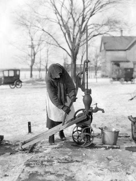 A bundled-up woman hand pumps water from a well into a pail. The ground is covered with ice and snow. Two cars and a farmhouse appear in the background.