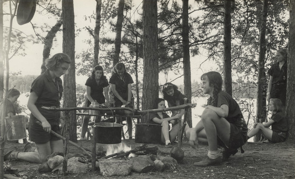 Girls with camp fire. The lake and far shoreline are in the distance.