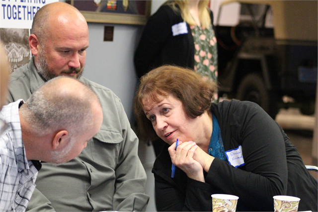 Glenda Finstad chats with Robert Quené, left, and her son, Brian Finstad, as they write down story ideas during the session.