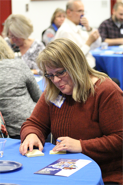 "A woman writes down some favorite ideas about the Superior area on a Post-It note during the Society's ""Share Your Voice"" session on Oct. 1, 2018 in Superior."