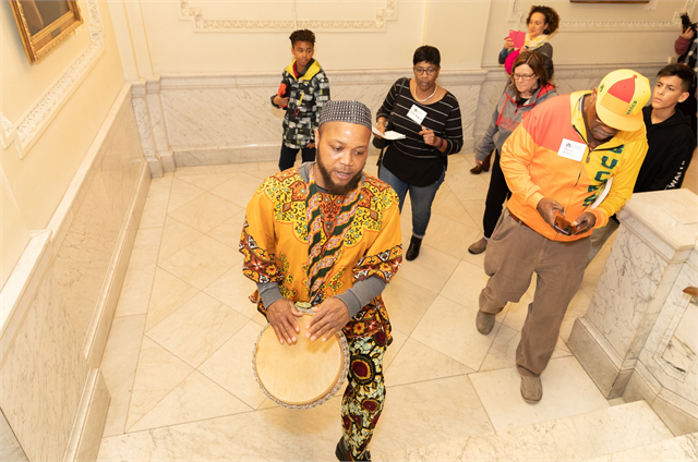 Decked out in traditional Ghanain Kente cloth, drummer Edi Gbordzi leads a processional up the marble stairs of the Wisconsin Historical Society's headquarters to the library reading room, where curators displayed rare African American artifacts.