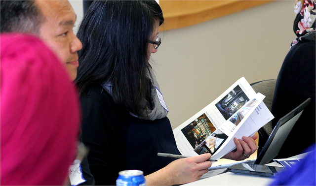 "Nan Kim, of the UW-Milwaukee Department of History, examines new museum concept exhibit design renderings during the Wisconsin Historical Society's ""Share Your Voice"" multicultural listening session May 15, 2019 in Greenfield."
